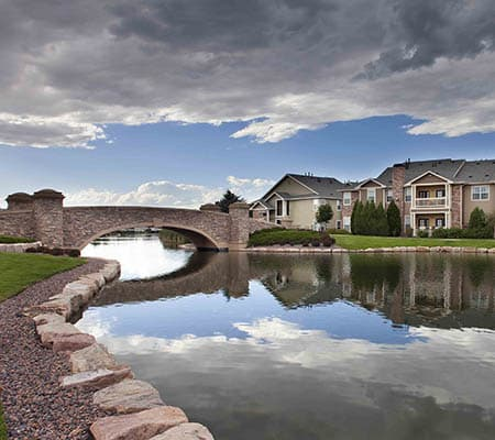 lake surrounding property, bridge over water at Gateway Park Apartments in Denver