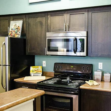 Renovated Brown Custom Kitchen Cabinetry with Stainless steel appliances at ((location_name}}