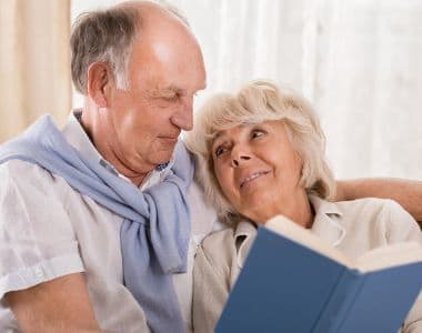 A happy couple reading together at All American Assisted Living at Washington Township
