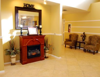 Hallway with a warm fireplace at Valley Crest Memory Care in Apple Valley, CA