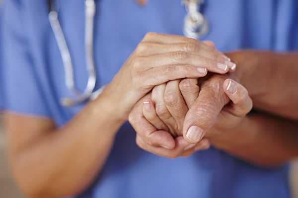 Caretaker holds the hand of a resident at Sun City Senior Living