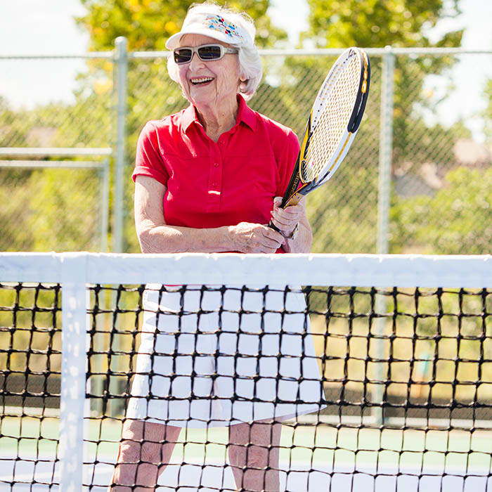 Senior playing tennis at Holly Creek Retirement Community