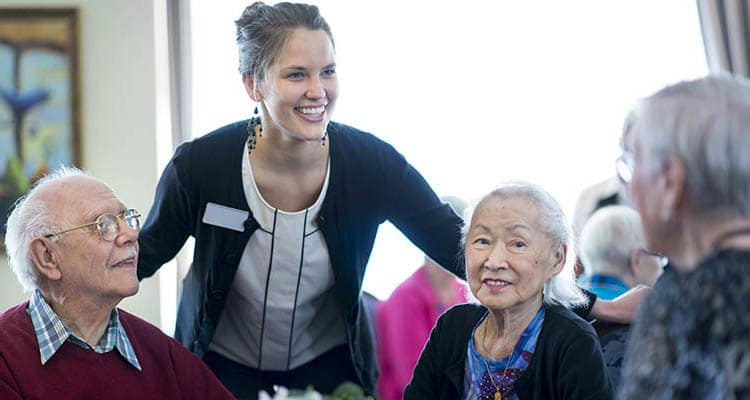A friendly staff member chats with residents at Pine Grove Crossing in Parker, Colorado