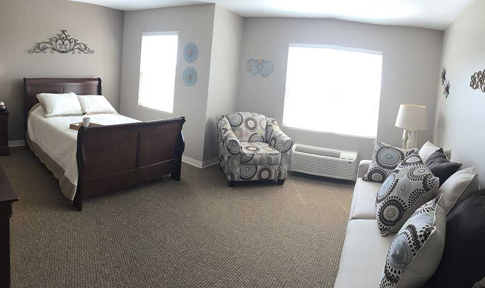 Big windows provide lots of natural light in the bedrooms at RobinBrooke Senior Living
