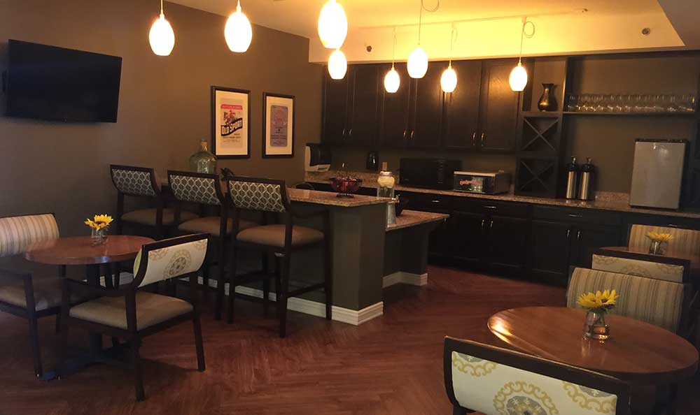 A dimly lit cafe at RobinBrooke Senior Living provides comfort and relaxation while enjoy a meal.