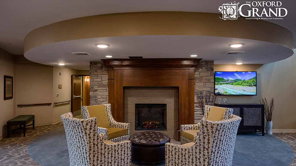Grab a book and read by the fireplace at The Oxford Grand Assisted Living & Memory Care in Kansas City, Missouri