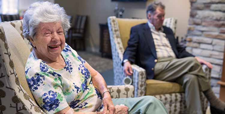 Residents enjoy time by the fireplace at The Oxford Grand Assisted Living & Memory Care