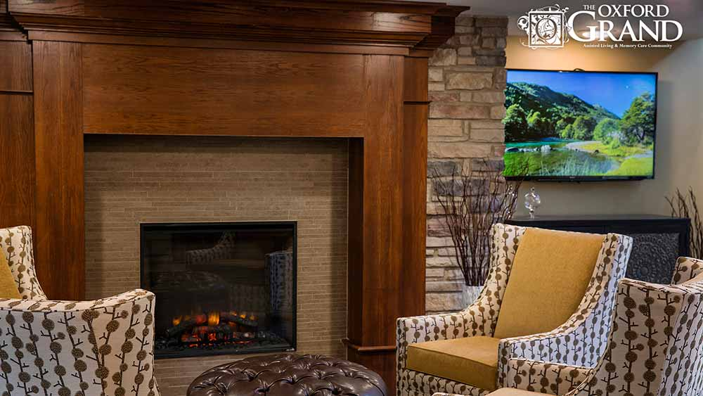 Gather with friends by the fire at The Oxford Grand Assisted Living & Memory Care in Kansas City, Missouri