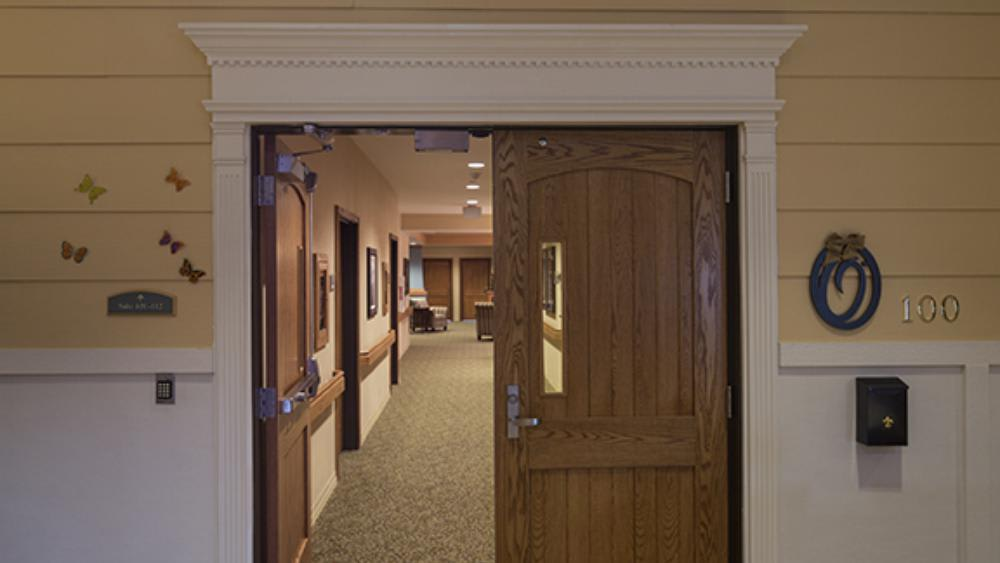 Wooden double doors leading into the community at Oxford Glen Memory Care at Grand Prairie in Grand Prairie, Texas