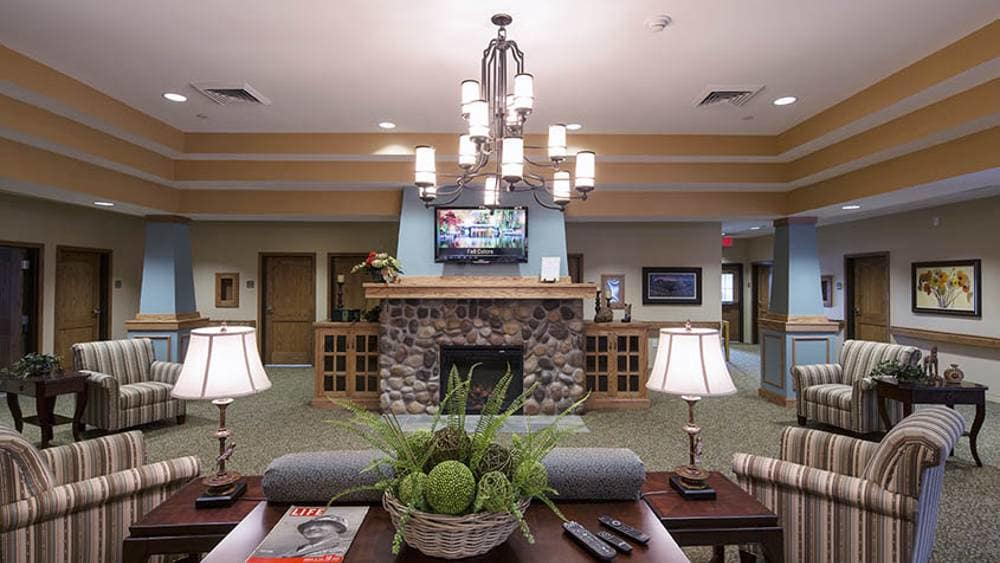 Living room with fireplace at Oxford Glen Memory Care at Sachse in Sachse, TX