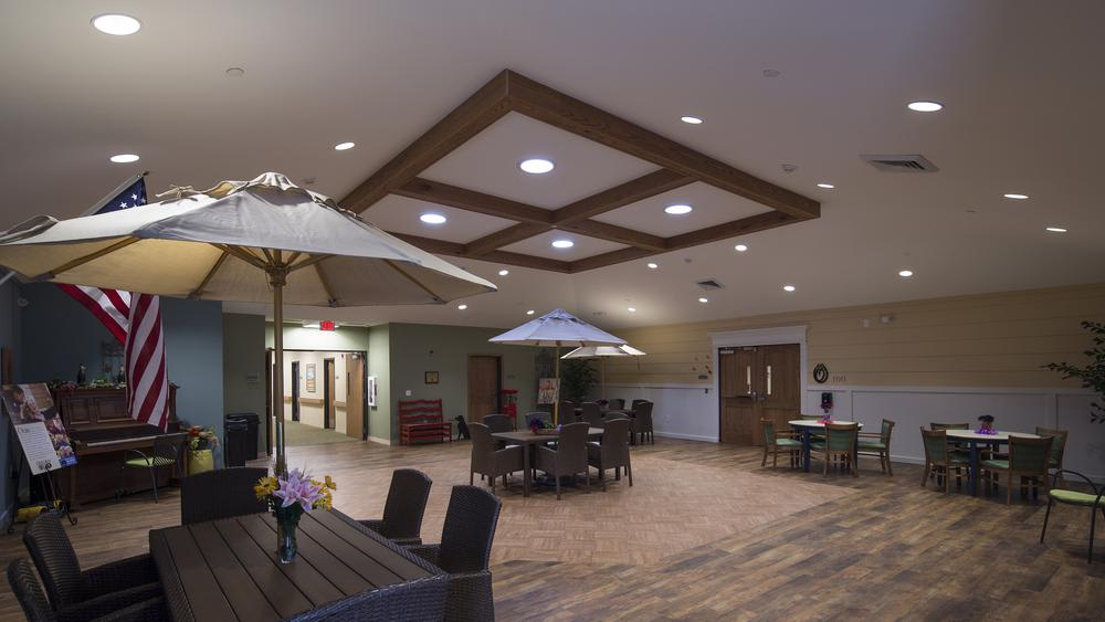Indoor lounge with outdoor seating and hardwood floors at Oxford Glen Memory Care at Grand Prairie in Grand Prairie, Texas