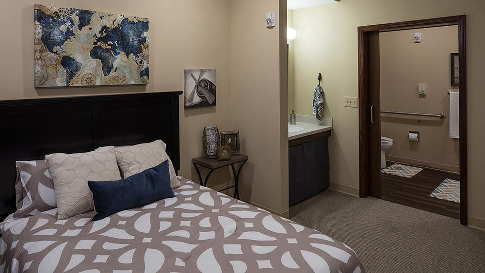 Bedroom in a senior apartment at The Oxford Grand Assisted Living & Memory Care in McKinney, Texas