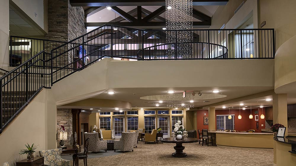 Reception area with stairs leading to the second floor at The Oxford Grand Assisted Living & Memory Care in McKinney, Texas
