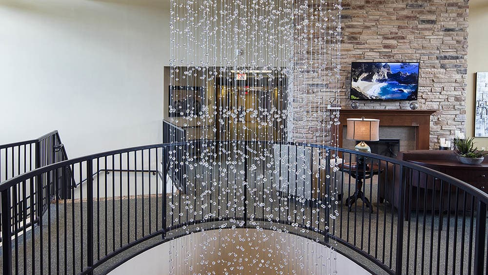 long crystal chandelier spanning into the first floor of The Oxford Grand Assisted Living & Memory Care in McKinney, Texas