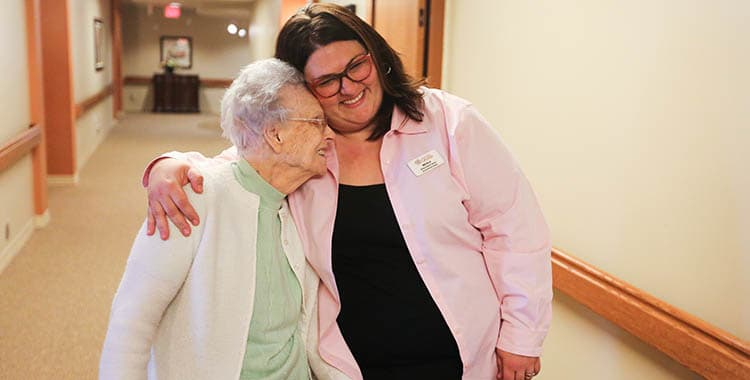 caregiver and resident walking down a hallway at The Oxford Grand Assisted Living & Memory Care