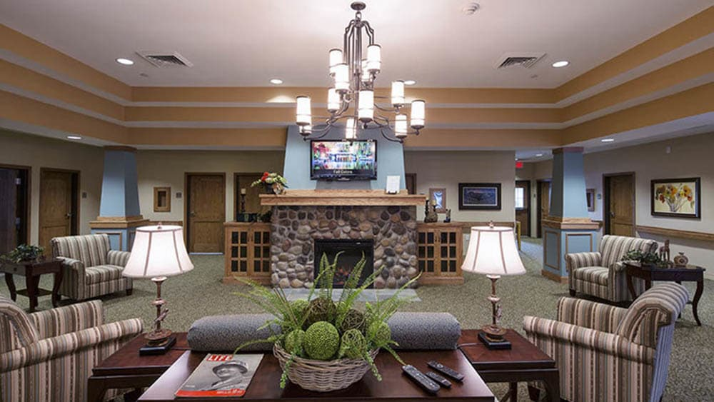 Lounge area with lots of seating and a chandelier at Oxford Glen Memory Care at Carrollton in Carrollton, Texas