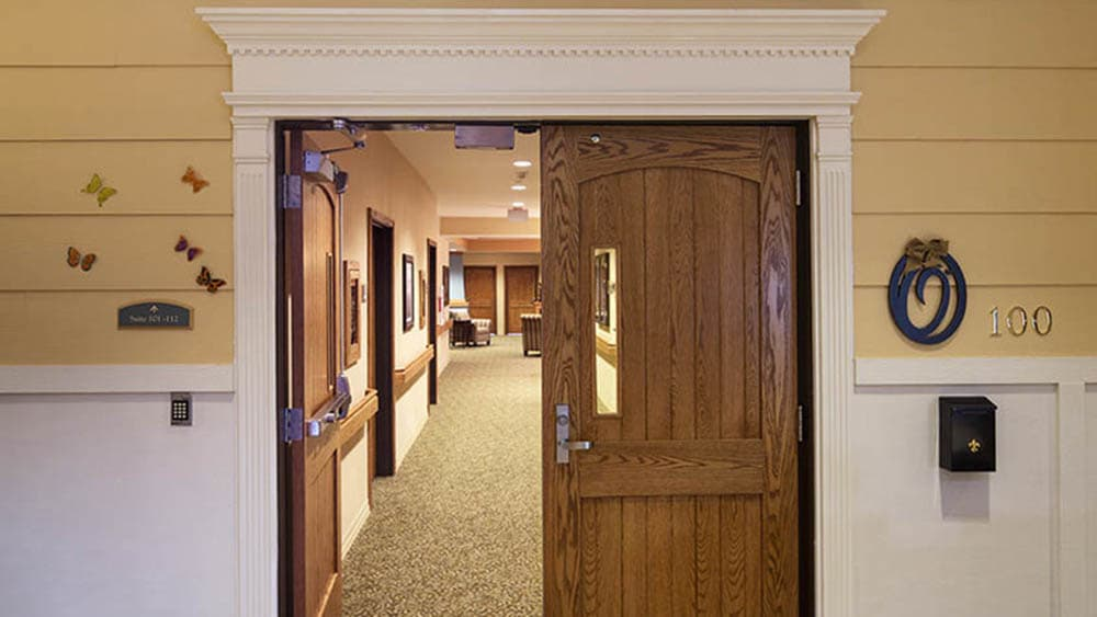 wooden double doors leading into Oxford Glen Memory Care at Carrollton in Carrollton, Texas