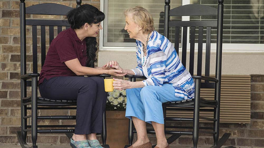 caretaker and resident having copy at Oxford Glen Memory Care at Carrollton