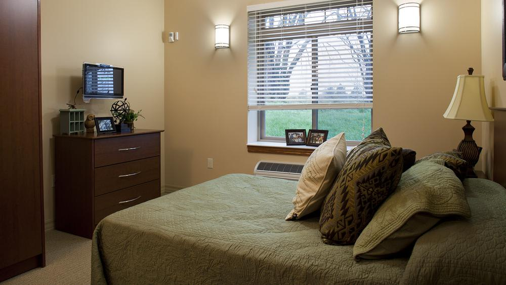Furnished bedroom in a senior apartment at Glen Carr House Memory Care in Derby, Kansas