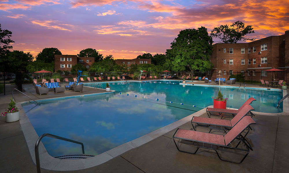 Our swimming pool with sun chairs at twilight in Mount Rainier, MD