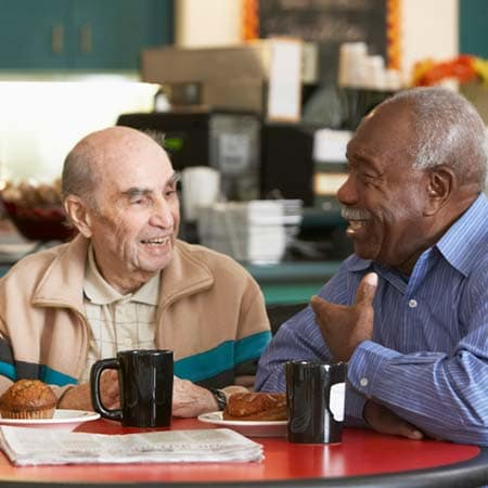 A resident having coffee with a friend at The Legacy at Hawthorne Park in Greenville, South Carolina