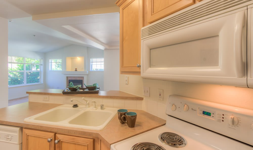 Closeup view of kitchen with white appliances and updated cupboards at Bradley Park Apartments in Puyallup
