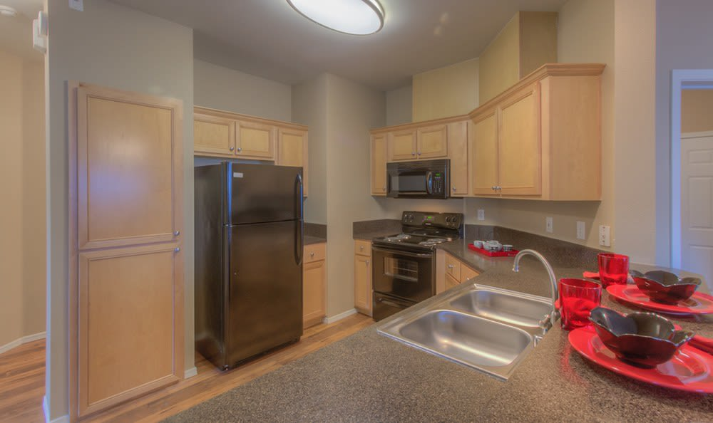 Modern kitchen with black appliances and new cupboards at Bradley Park Apartments in Puyallup