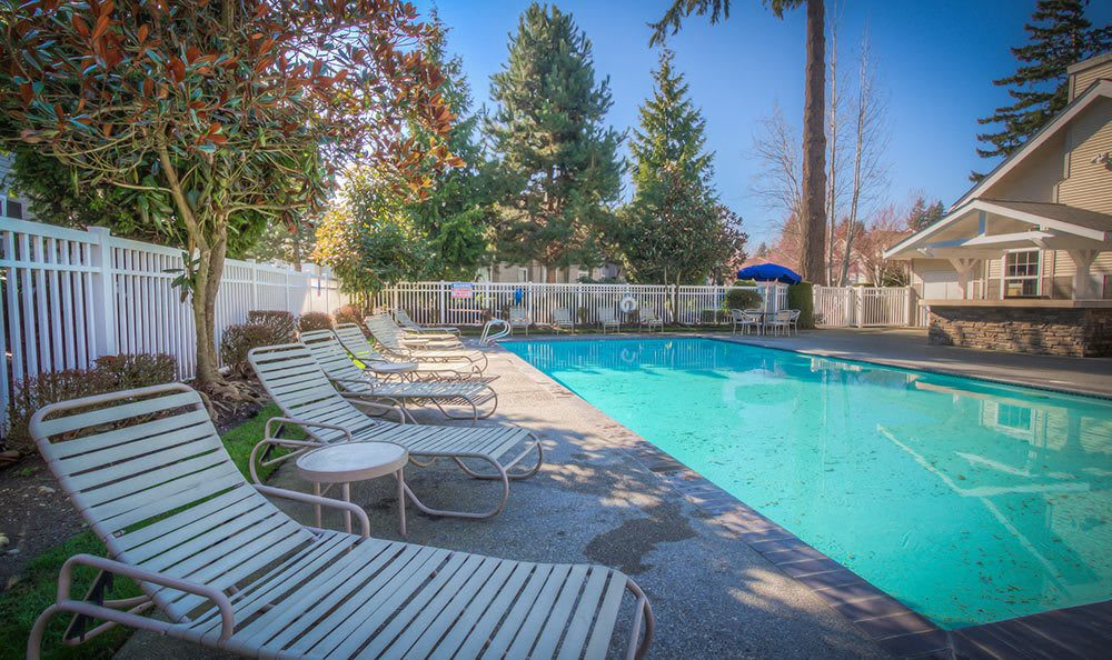 Swimming pool and lounge seating at Bradley Park Apartments in Puyallup