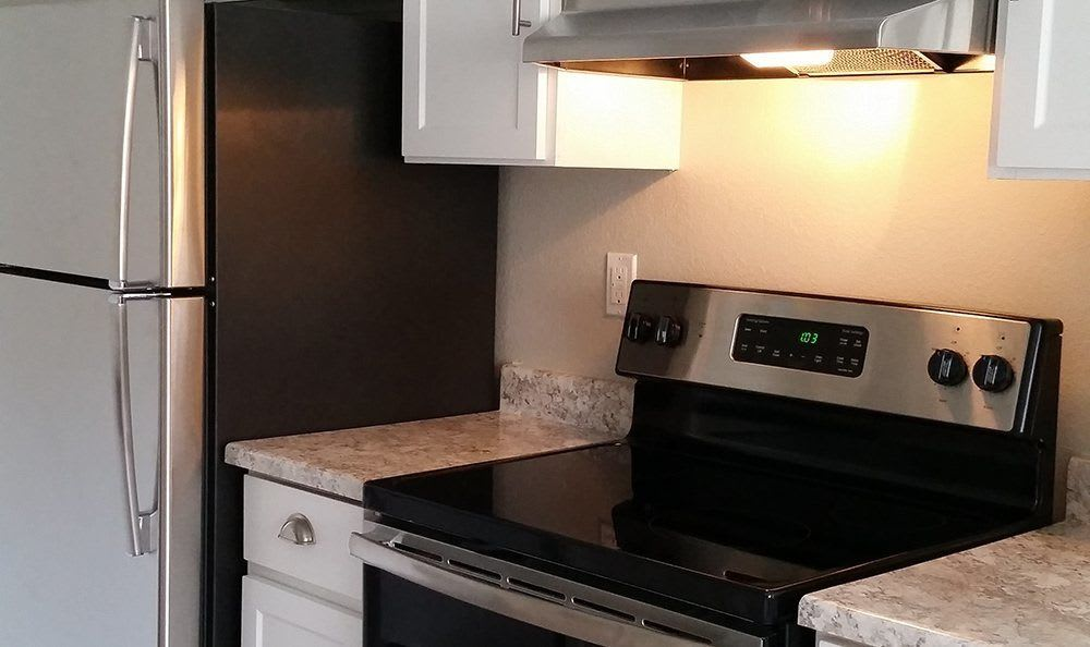 Black appliances and modern conveniences in Chestnut Hills Apartments model apartment home's kitchen in Puyallup, Washington