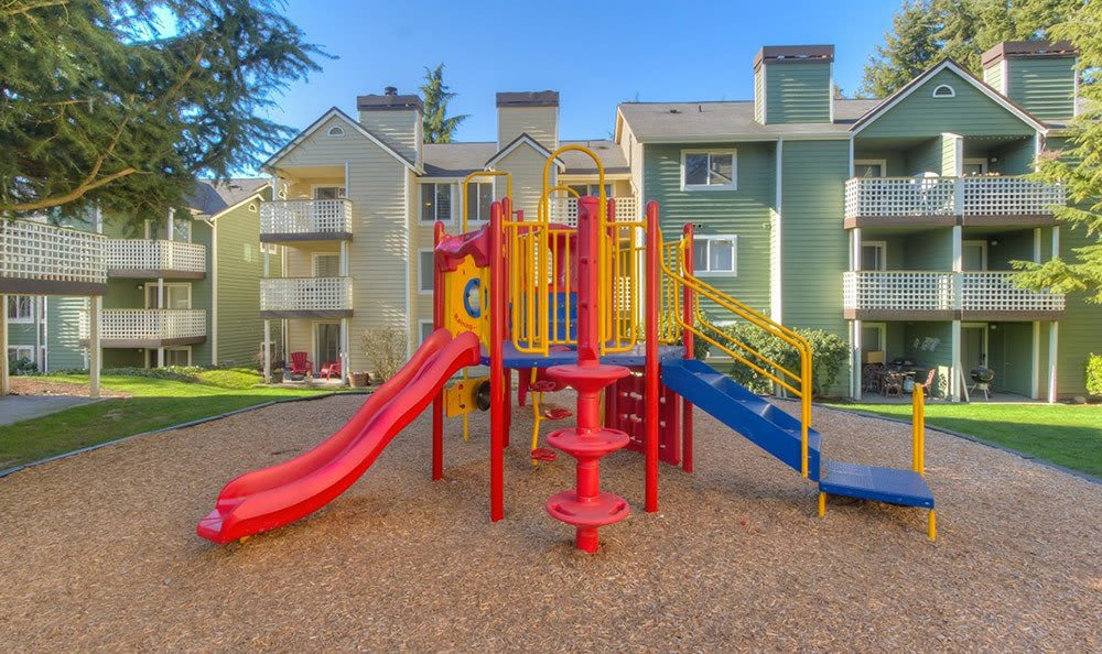 On-site playground near apartment buildings at The Hamptons Apartments in Puyallup, WA