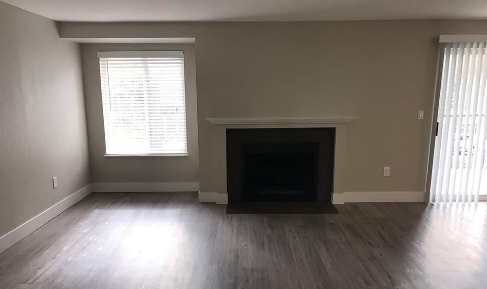 Model apartment home's living room, showcasing hardwood floors, natural light, and fireplace at The Hamptons Apartments in Puyallup, WA