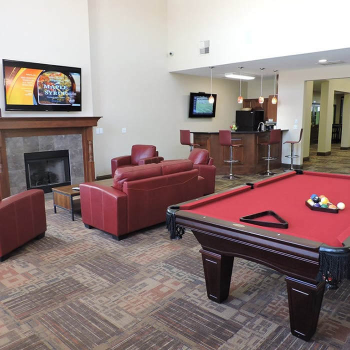 Interior clubhouse view at Village at Seeley Lake, showcasing comfortable seating and billiards table