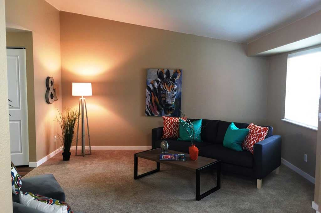 Well-decorated and spacious living room in model apartment home at Village at Seeley Lake in Lakewood, Washington