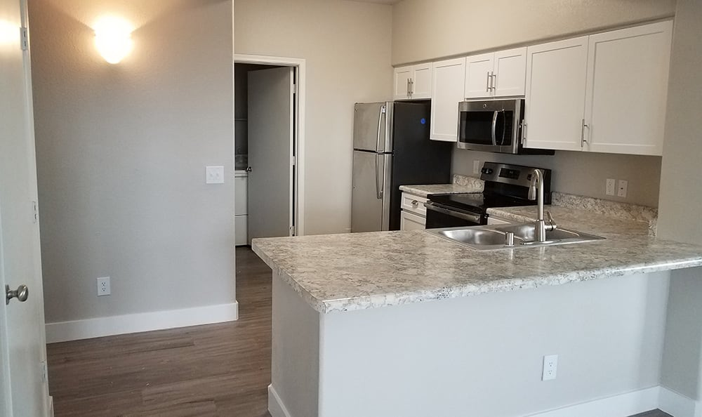 Wide-angle view of kitchen in model home at The Retreat Apartments in Phoenix on a bright morning