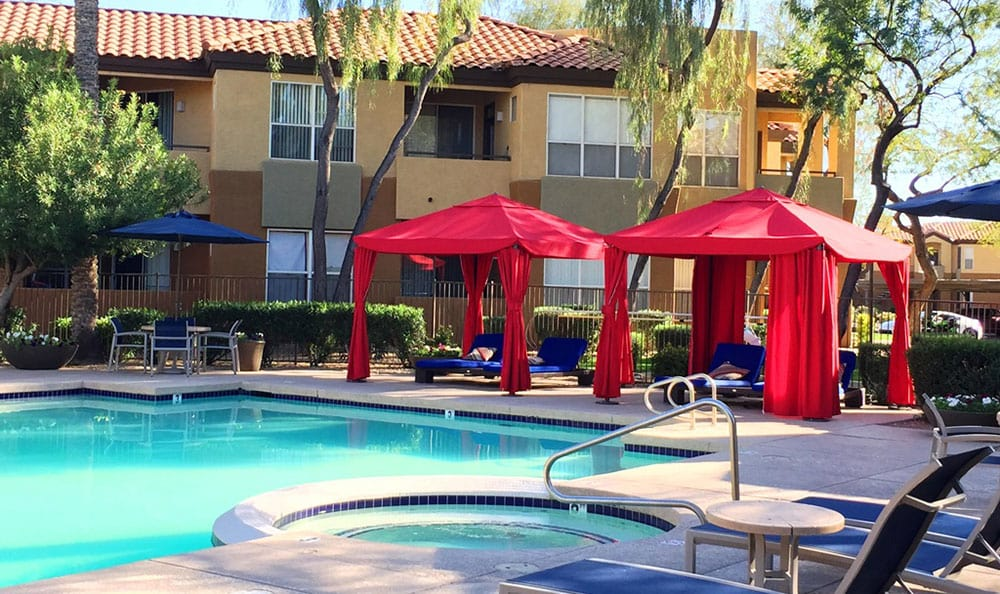 Gorgeous swimming pool area with chaise lounges and shaded cabanas at The Retreat Apartments in Phoenix