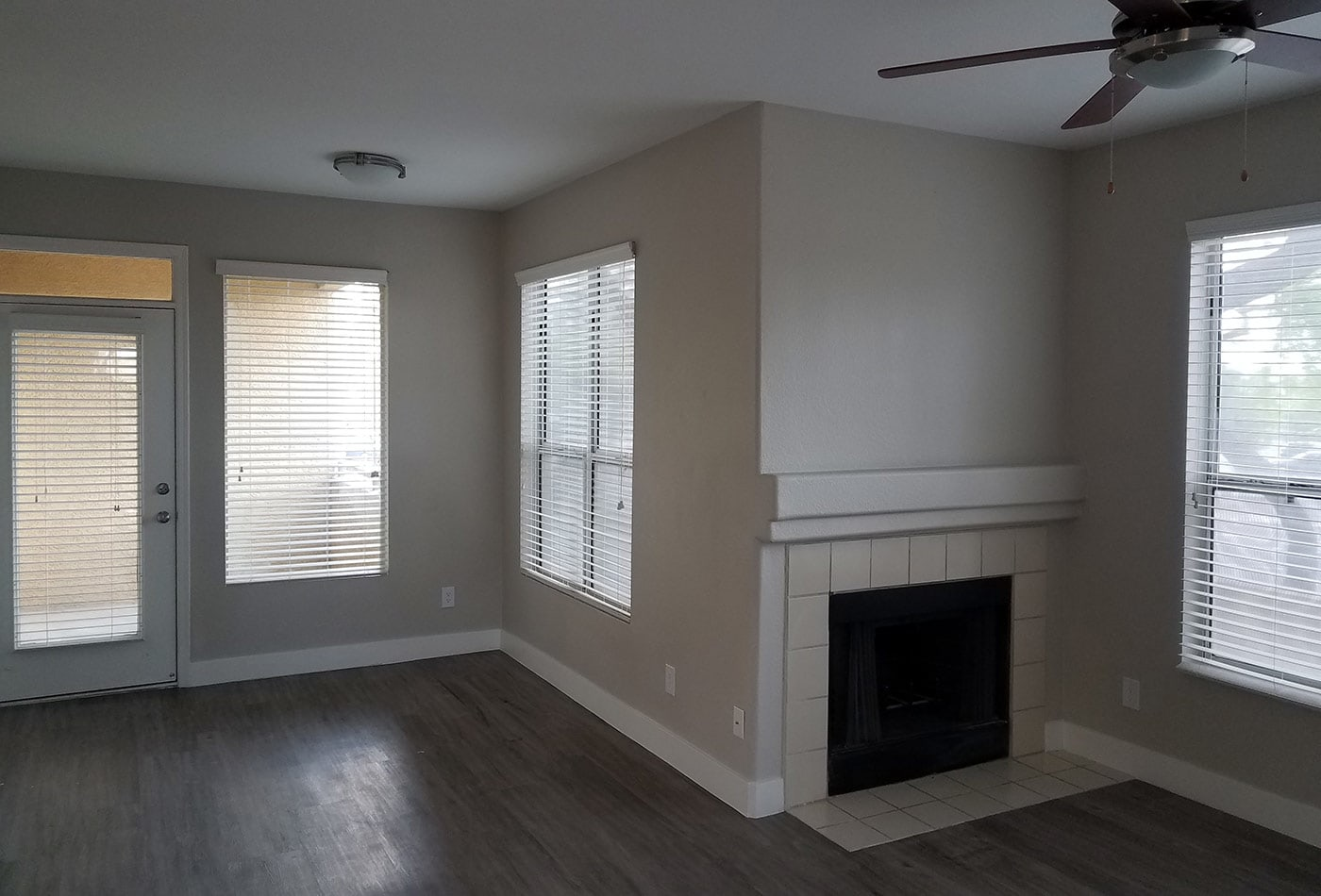 Hardwood floors and fireplace in model home living room at The Retreat Apartments