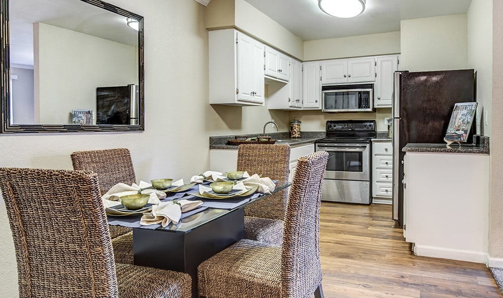Beautifully decorated model home's dining and kitchen areas - showcasing hardwood floors - at Aventerra at Dobson Ranch in Mesa