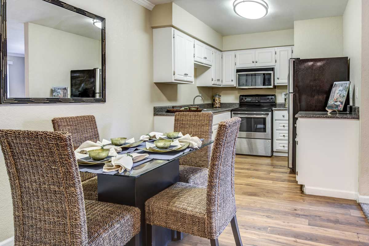 Modern kitchen and dining room in model apartment home at Aventerra at Dobson Ranch featuring hardwood floors