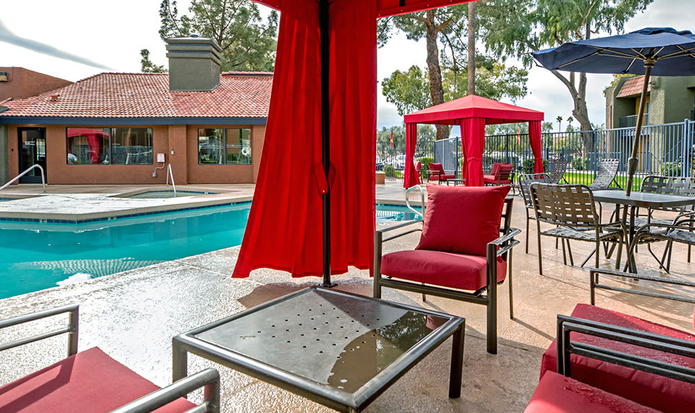 Another poolside view showing private cabanas and additional seating at Villetta Apartments in Mesa