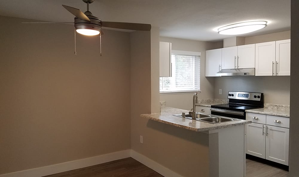 Upgraded ceiling fans and modern kitchen in model apartment home at Villetta Apartments in Mesa