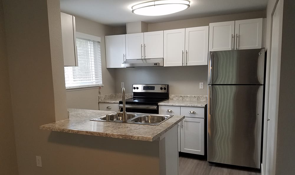 Modern kitchen with stainless-steel appliances at Villetta Apartments in Mesa