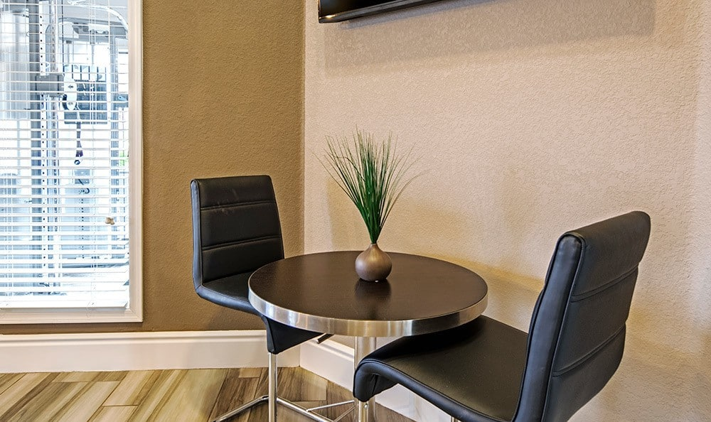 Seating and table near on-site fitness center at Villetta Apartments in Mesa