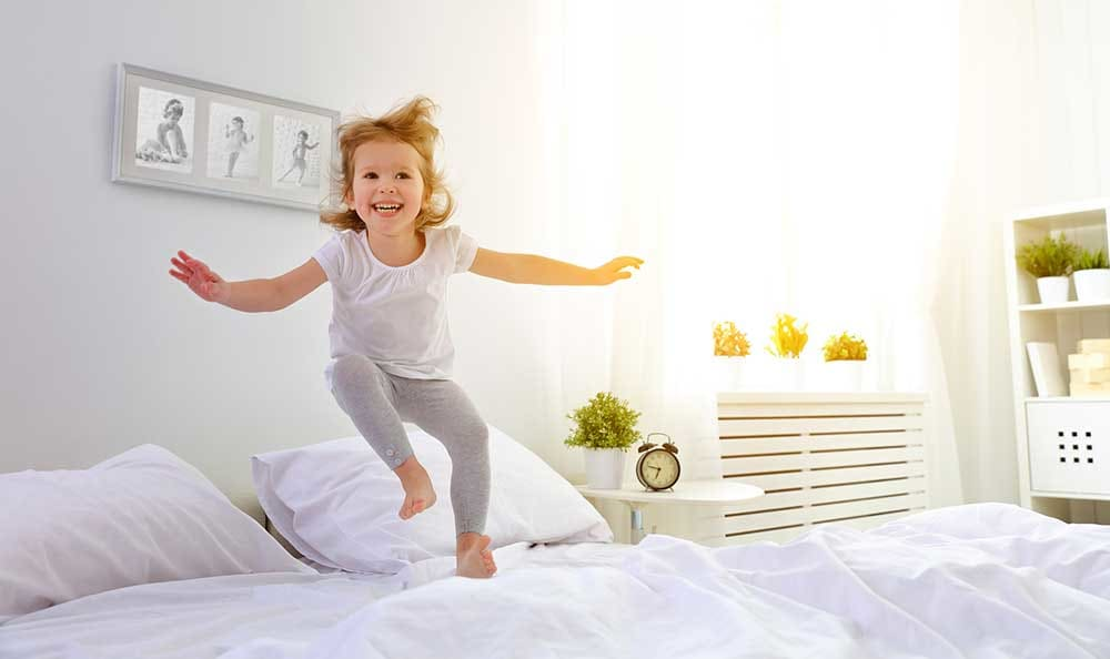 Child jumping on the bed at Columbia Commons