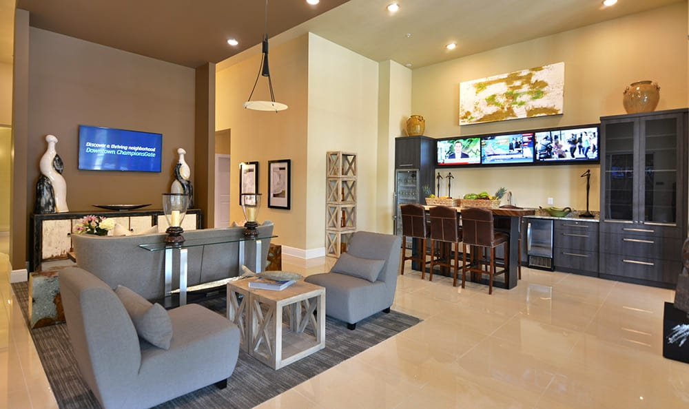 Wide angle view of The Gate Apartments clubhouse, including bar and tv area