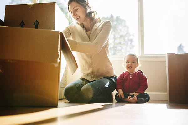 Mother and baby moving boxes