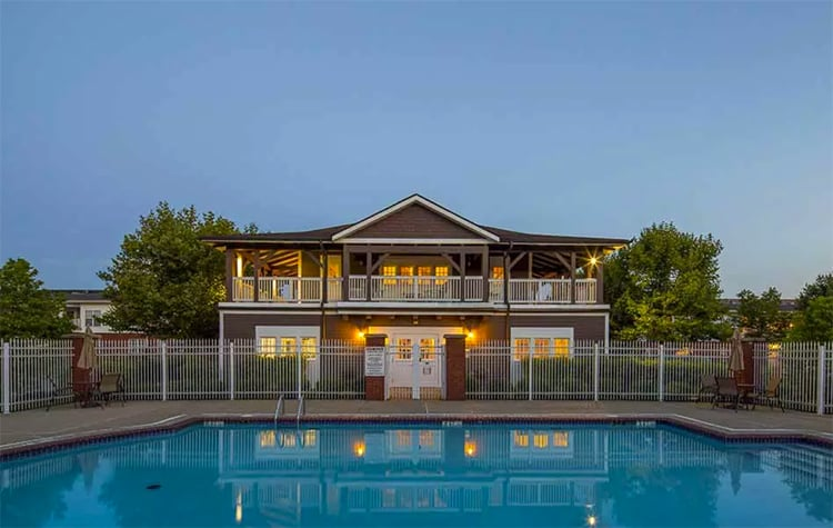 Beautiful view of the clubhouse at dusk from across the pool at The Waterfront Apartments in Munhall