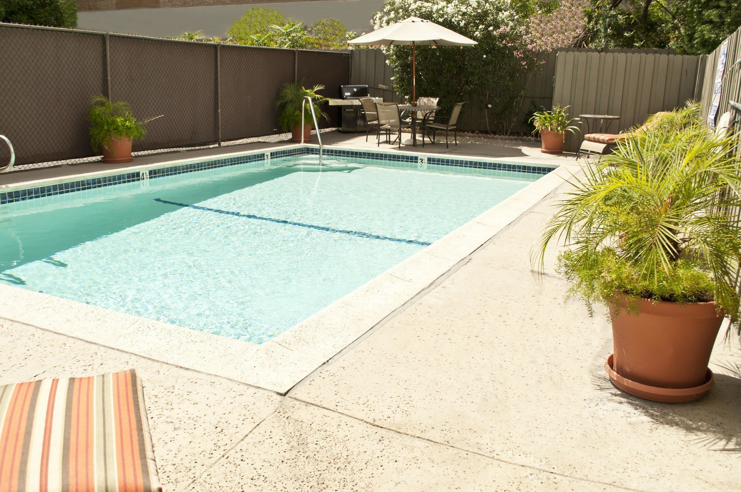 Outdoor pool with table and chairs at The Newporter in Tarzana, California