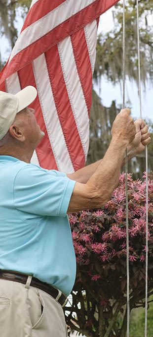 Resident raising the flag at Arbors Memory Care in Sparks, NV