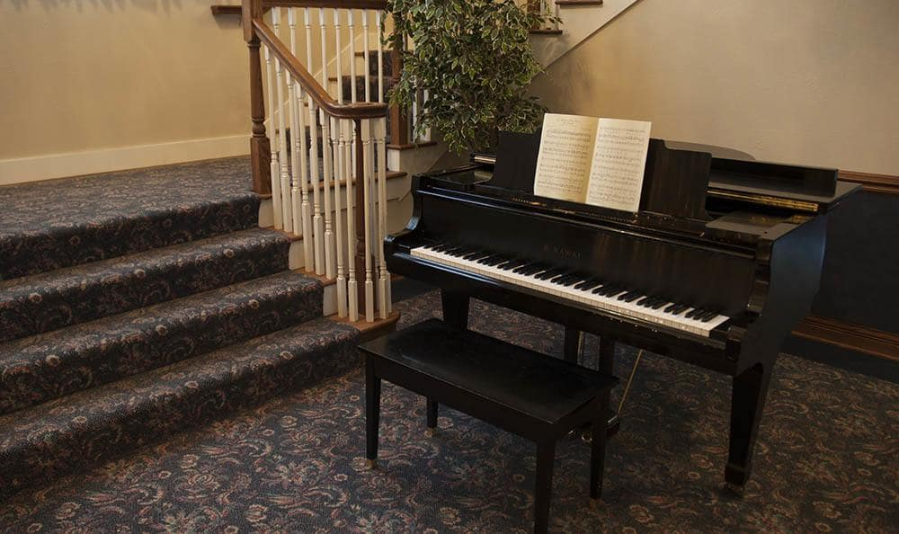 Piano sitting at the base of a staircase in Randall Residence of Decatur in Decatur, Illinois