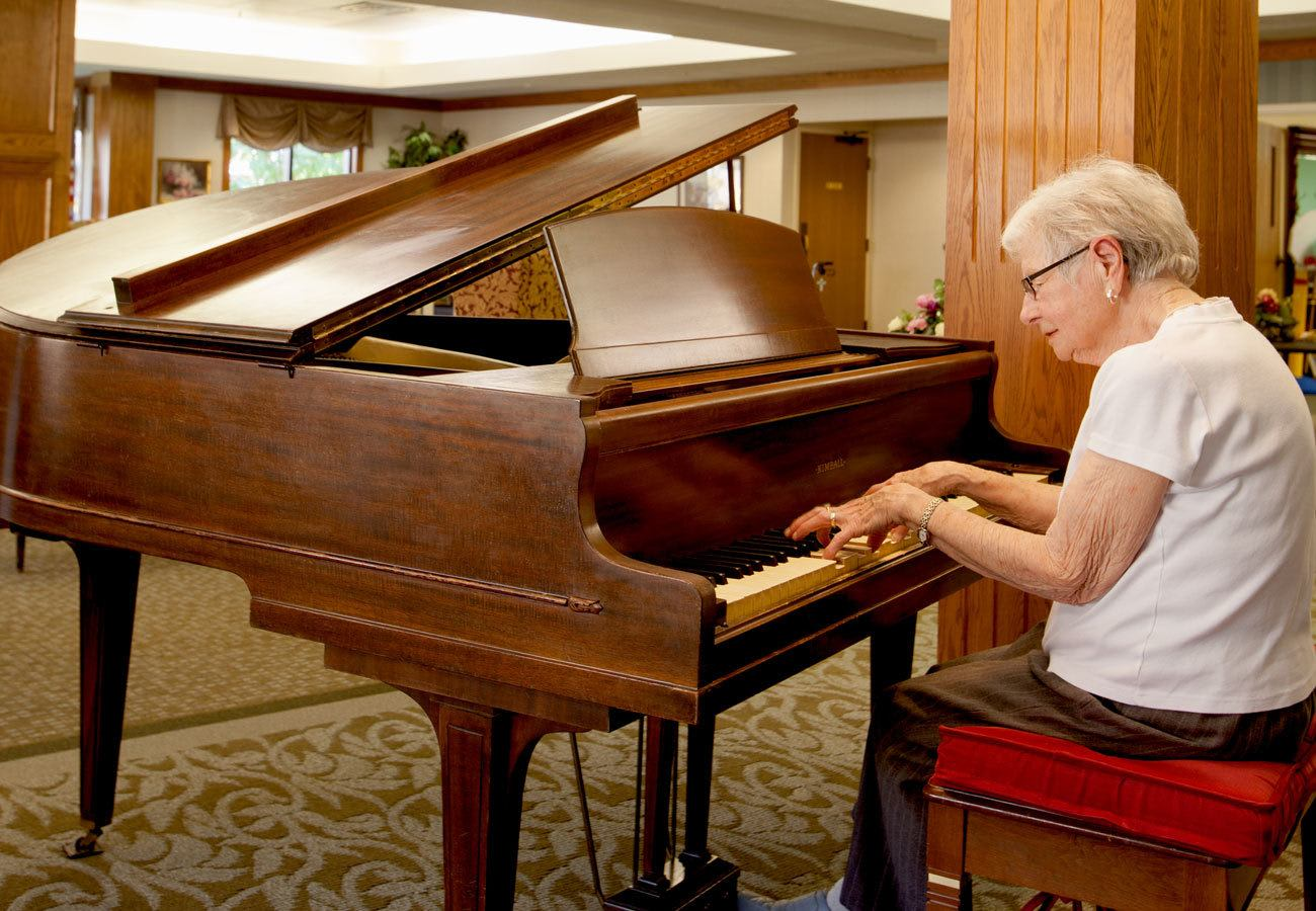 Resident playing the piano in a lounge at Villa at the Lake in Conneaut, Ohio